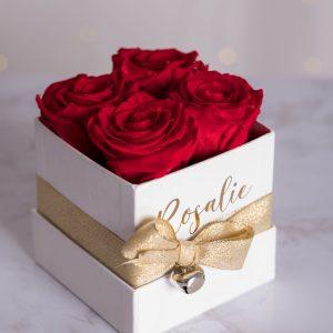 scatola bianca quadrata con 4 rose stabilizzate rosse e nastro dorato su tavolo di marmo bianco