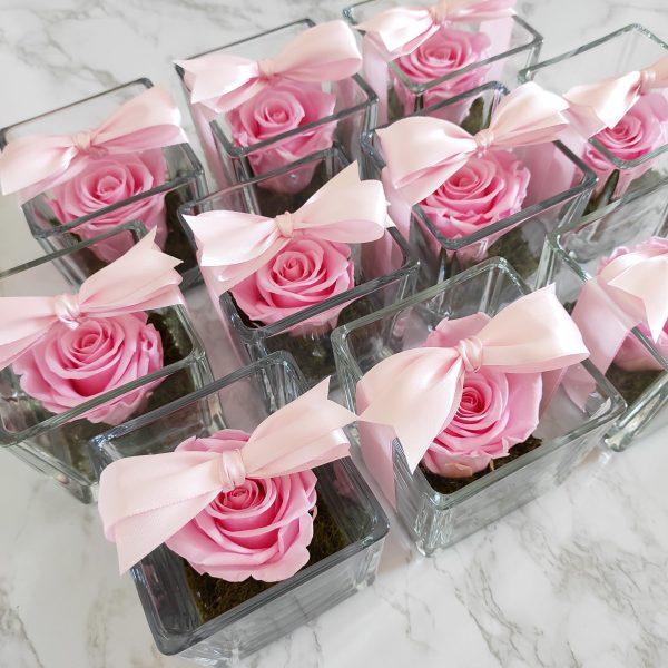 bomboniere nascita bambina con rose stabilizzate rosa e fiocco rosa sopra su tavolo