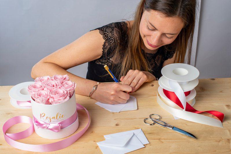 donna che scrive un messaggio accanto a scatola di rose stabilizzate e nastri di raso