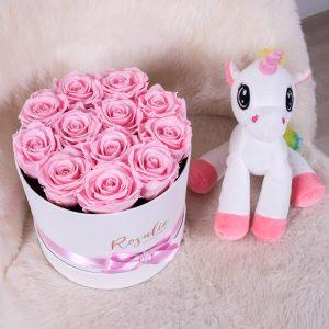 scatola tonda con 12 rose stabilizzate di color rosa accanto a pupazzo a forma di unicorno