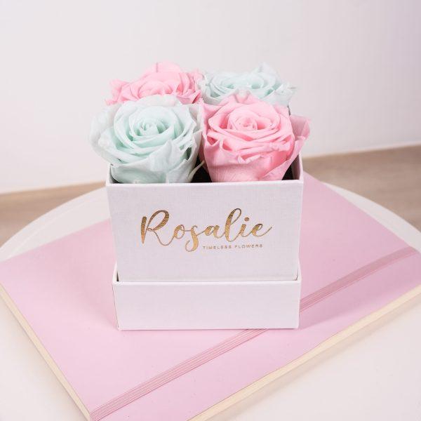 scatola quadrata con 4 rose stabilizzate di color rosa e verde menta su quaderno rosa e tavolo bianco