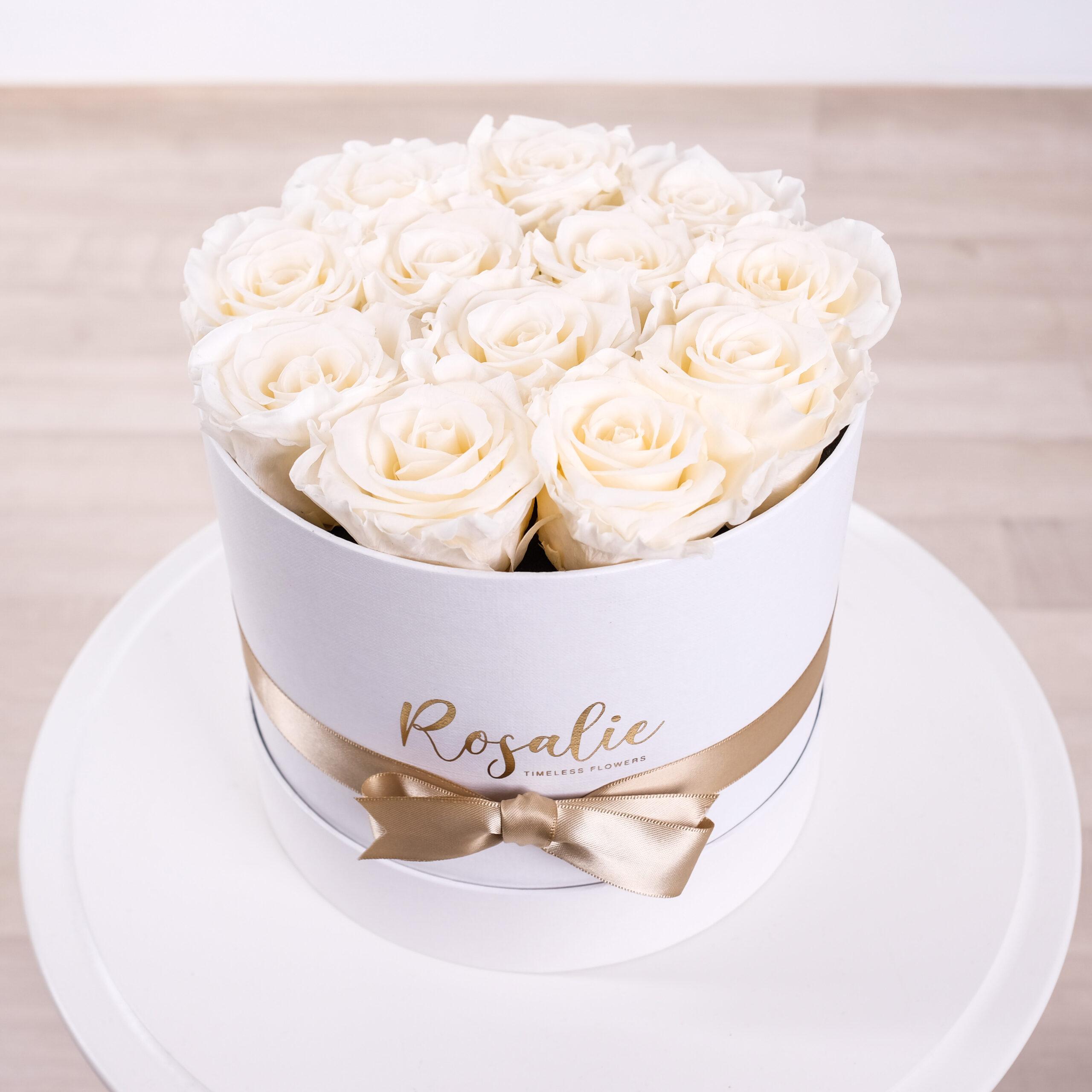 scatola con 12 rose bianche panna e nastro dorato su tavolino bianco