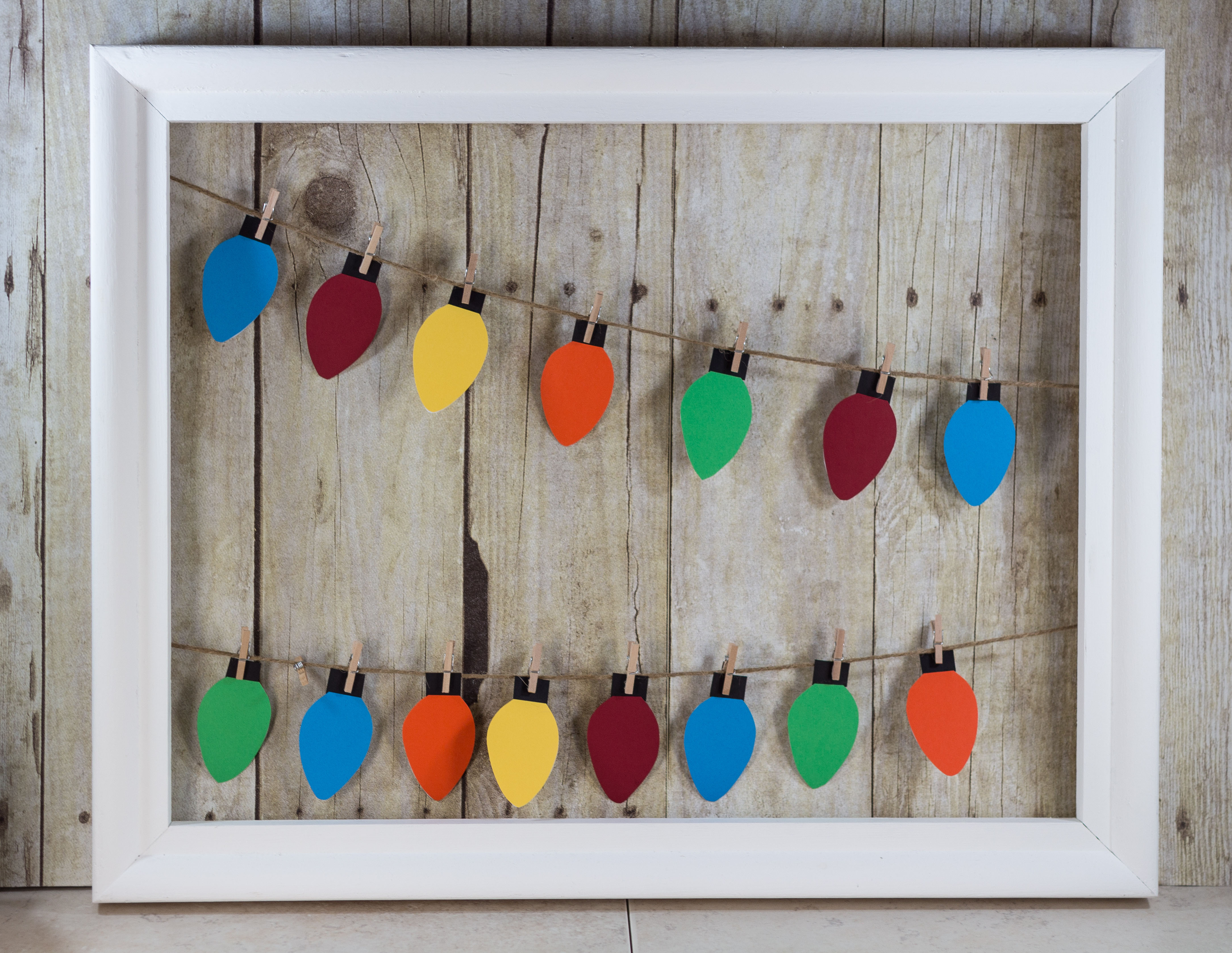 Learn how to make your own paper Christmas lights hanging display! | http://www.roseclearfield.com