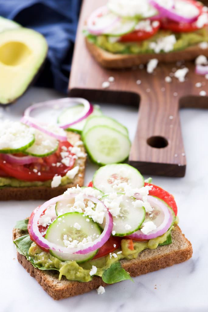 Mediterranean-style avocado toast with cucumber, tomato, red onion, and feta cheese. via With Salt and Wit #Mediterraneancuisine #avocadotoast #healthybreakfast | https://www.roseclearfield.com