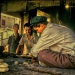 Uyghur men bake bread in tandoor oven