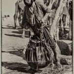 Touareg man carries water to camels in the Mali's Sahara
