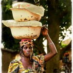 beautiful African woman carries a headload of laundry