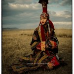 Mongolian woman in costume of Queen stares into the distance