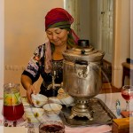 A Kazakh woman serves tea from a samovar