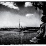 dramatic black and white landscape of Fortress of Peter and Paul with stanchion of bridge over river Neva