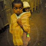 Ethiopia: A small girl carries an infant on her back