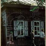 Siberian street scene with russian house and passerspby