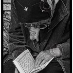 an elderly woman reads her prayerbook, her glasses falling off her face, workworn hands keeping her place on the page