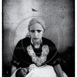a Berber woman holds her newborn baby on her lap