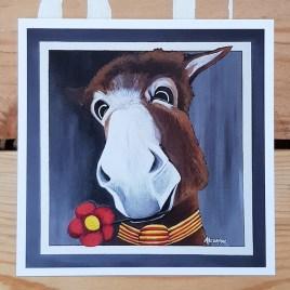 La carte postale de Joli Coeur représente le portrait d'un âne très charmant avec sa fleur à la bouche et son foulard catalan.