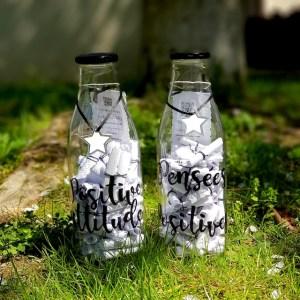 """Présentation de deux bouteilles en verre remplies de 60 pensées positives. Une avec l'inscription : """"Positive attitude"""" et l'autre """"Pensées positives"""""""
