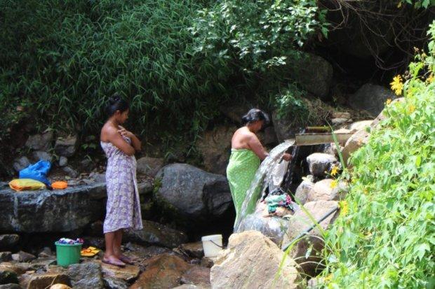 Washing laundry in waterfall, Sri Lanka tea country