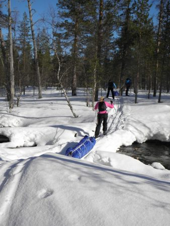 Ski tour in Lapland, crossing a river in Lankojärvi