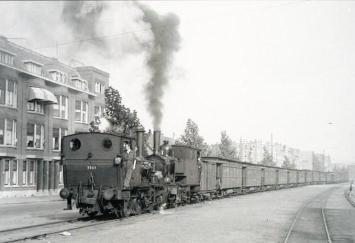 Op de putselaan is een trein met werklieden onderweg naar Heijplaat en de verder gelegen havens, 10-1949 (foto: J.J. Overwater)
