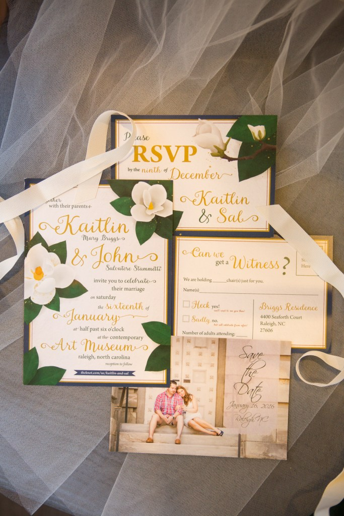 wedding invitation suite with blue green and magnolias save the date with couple on steps in front of capitol building in downtown raleigh