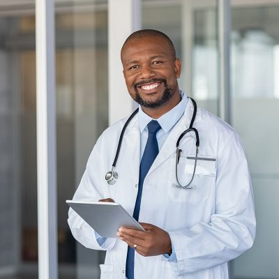 Portrait of confident mature black doctor consulting digital tablet and looking at camera. Smiling african american doctor with stethoscope using tablet at medical clinic. Happy healthcare worker using computer at modern hospital.