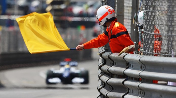 A marshall waves a yellow flag at the Monaco Grand Prix