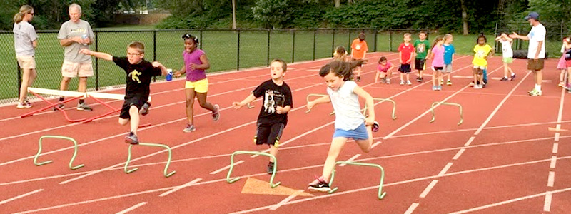 Kids jumping hurdles on the track