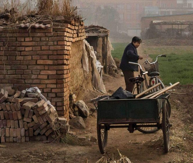 Изображение из деревни Лян: женщина тянет тележку рядом с кирпичом.