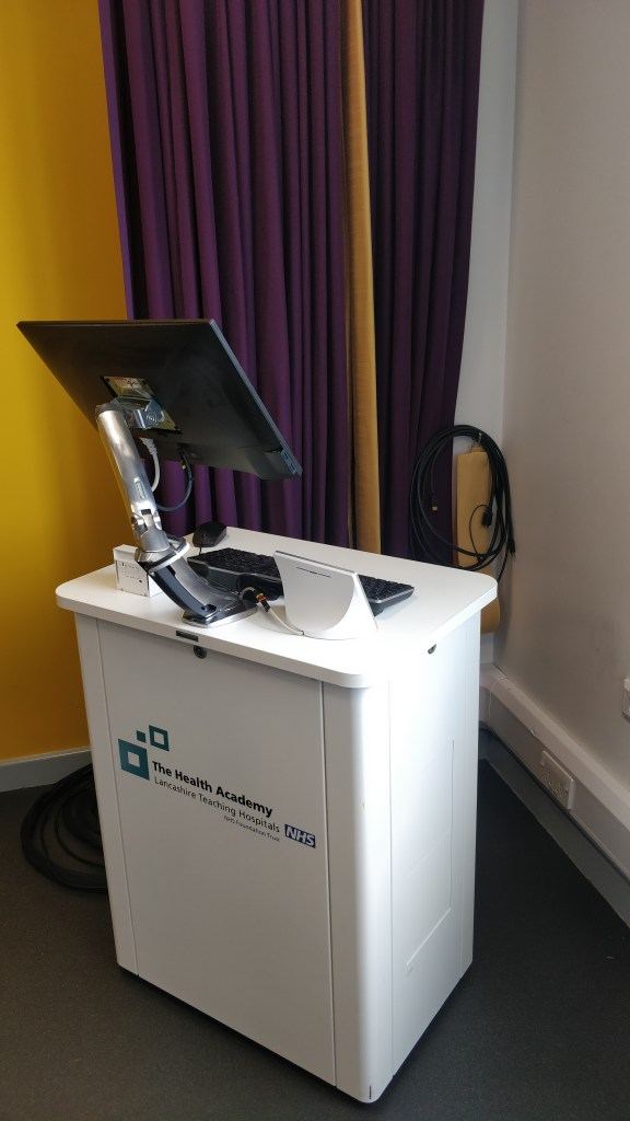 Picture of a lectern with a monitor,, keyboard, mouse, touchpanel and input plate on.