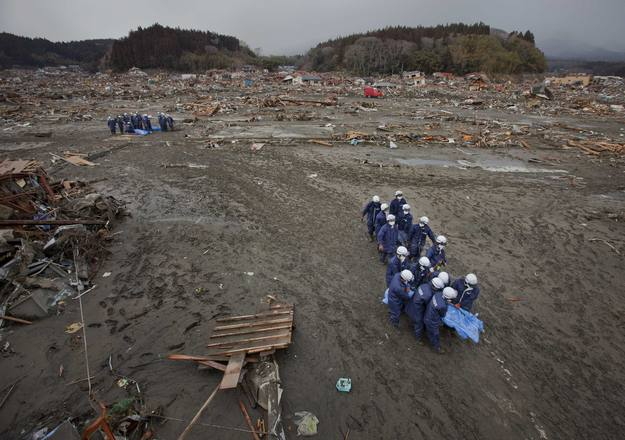 Operarios retiran el cuerpo sin vida de una de las víctimas del tsunami en Rikuzentakata
