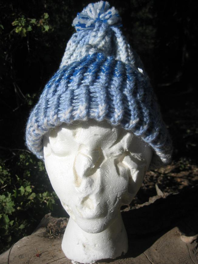 Esmerelda is modeling a hat with a finished edge. The color scheme of the hat includes white and various shades of blue. Best of all, the hat sports a white and blue pompom on top. This hat can be yours for $13, including postage.