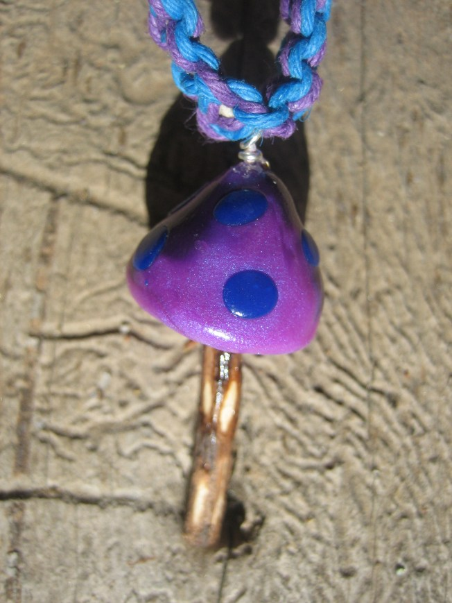 If I had to pick a favorite of the mushroom pendants, this would be it. The cap is made from purple and blue clay. The stem is made from a tiny stick. That's right! The stem is a piece of wood. I hung the pendant from a necklace of purple and blue hemp. The necklace is 20 inches. The price is $23, including postage.