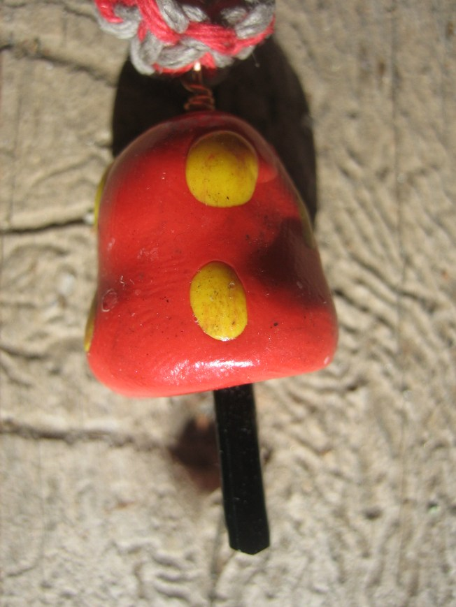 This amanita-esque mushroom pendant is super cute. The cap is made from red and yellow clay. The stem is made from a crystal (!) maybe tourmaline. I used red and variegated earth-tone hemp to make the necklace, which is 20 inches. The cost is $23, including postage.