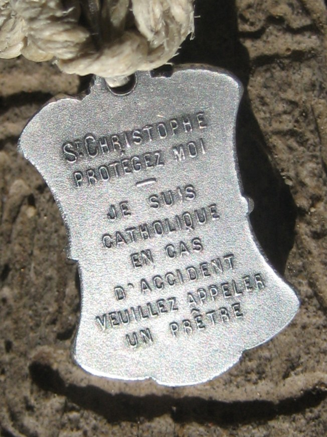 This is a closeup of the back of the medal. I think it says something like, I'm Catholic. In the event of an emergency, call a priest.
