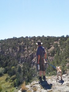 A man and dog stand on a rock overhang. Both look down into a green canyon.