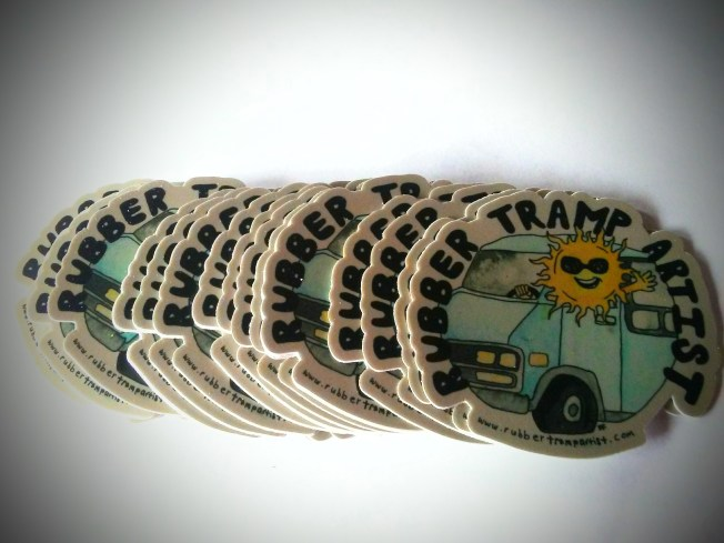 Stickers are fanned out across a table. Each sticker has the words Rubber Tramp Artist across the top. Each sticker shows a smiling sun sitting in the drivers seat of a large blue van. The sun wears sunglasses and has its head popped out of the window. The sun has one hand on the steering wheel and waves with the other hand.