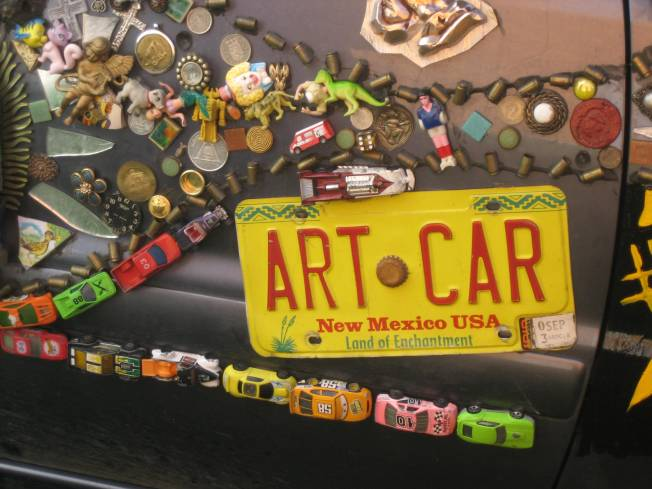"Art car is decorated with Matchbook cars, bullet casings, small plastic toys and a yellow New Mexico license plate that read ""Art Car."""