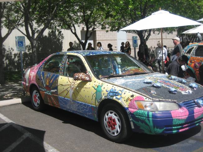 An art car is brightly painted with images of bugs and flowers. The Blessed Virgin Mary is painted on the hood.