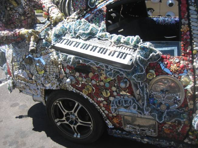 A keyboard projects from the back passenger side door of a meticulously decorated art car.
