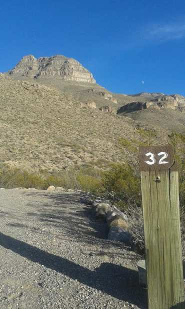 Campsite post in foreground has number 32 on it. Mountain and blue sky in background.