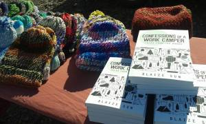 Brightly colored handmade hats and copies of the book Confessions of a Work Camper: Tales from the Woods sit on a table.