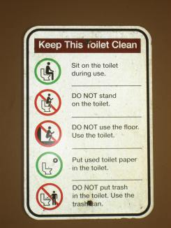 "Sign reads, ""Keep this toilet clean."" The sign gives instructions (with corresponding drawings) on how to properly use the pit toilet. Instructions include ""Sit on the toilet during use. DO NOT stand on the toilet. DO NOT use the floor. Use the toilet. Put used toilet paper in the toilet. Do NOT put trash in the toilet. Use the trash can."""