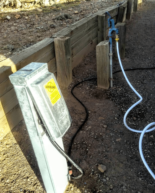 Hose connected to campground water spigot in background. Thick black electrical cord connected to campground electrical box in foreground.