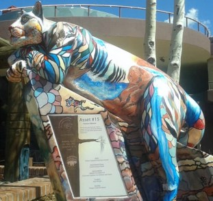 Sculpture of a reclining life size mountain lion painted bright colors