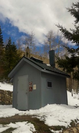 Forest Service outhouse with snow on the ground all around it