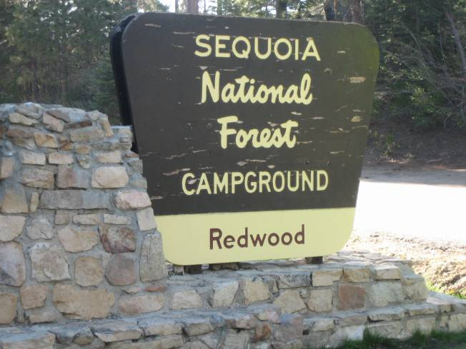 Peeling brown wooden sign reads Sequoia National Forest Campground Redwood.