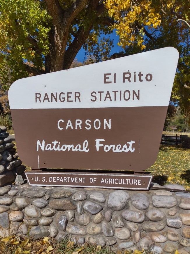 Brown and white wooden national forest sign reads, El Rito Ranger Station Carson National Forest U.S. Department of Agriculture
