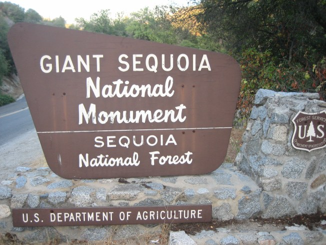 Brown wooden Forest Service sign reads, Giant Sequoia National Monument Sequoia National Forest U.S. Department of Agriculure