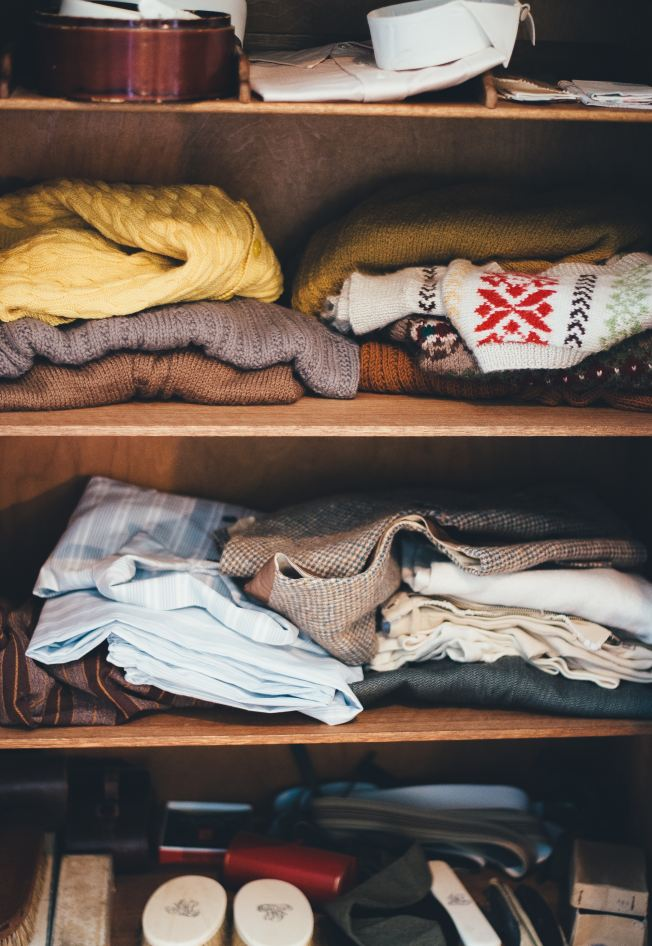 sweaters and shirts on shelves in a closet