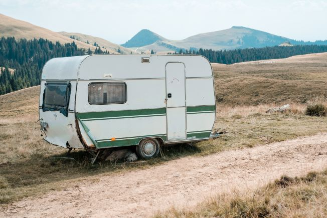 Small camper parked immediately to the side of a dirt road